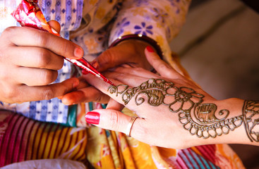 Painting hand with henna in flower design