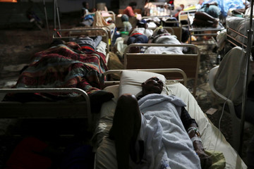 People injured in an earthquake that hit northern Haiti late on Saturday, sleep in a tent, in Port-de-Paix