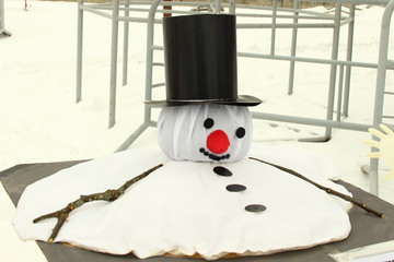 Global warming illustration - sculpture of a spreading sad snowman on a black background