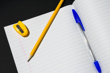 Photo of a fragment of a notebook in a line on which lies a pencil, pen and sharpener