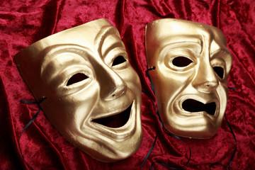 Tragicomedy masks on red velvet fabric