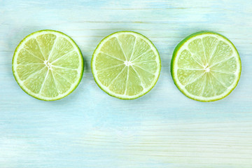 An overhead closeup photo of three lime slices on a teal blue background