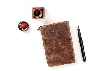 An overhead photo of an ink well with an old journal, with a nib pen and copy space, shot from above on a white background