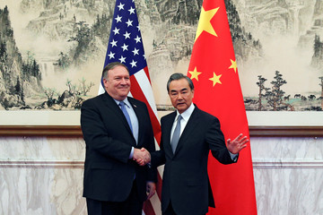 Chinese State Councilor and Foreign Minister Wang Yi shakes hands with U.S. Secretary of State Mike Pompeo before a meeting at the Diaoyutai State Guesthouse in Beijing