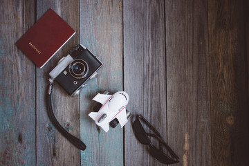 A passport, vintage camera, small aircraft and sunglasses on wooden background