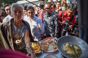 IMF Managing Director Lagarde buys traditional snacks from vendor during visit to area affected by earthquake in West Lombok