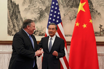 U.S. Secretary of State Mike Pompeo chats with Chinese Foreign Minister Wang Yi as they proceed to their meeting at the Diaoyutai State Guesthouse in Beijing