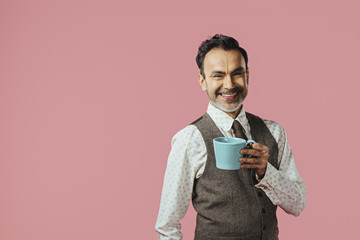 Smiling mature man holding coffee mug, isolated on pink studio background