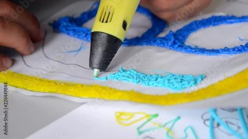 A persone drawing 3d pen close-up  The plastic thread melts