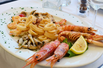 Shrimps squids and other seafood on a white ceramic plate in an Italian restaurant.