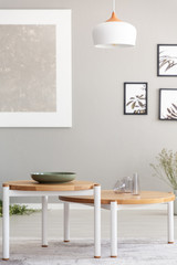 Lamp above wooden tables in grey living room interior with posters and mockup. Real photo