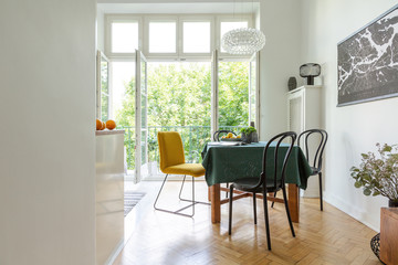 Dining chairs around a wooden table on a herringbone parquet floor of a white kitchen interior with open balcony