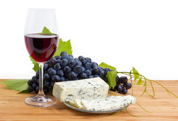 Red wine and blue cheese against of the blue grapes