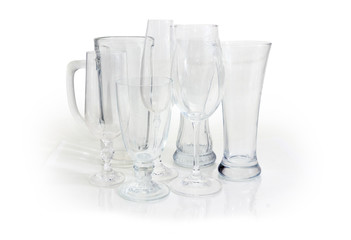 Different empty glass utensils on a white background