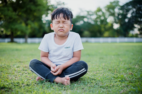 Asian children cute or kid boy sit for meditation with peace and relax in public park and wearing white dress with sunlight on white with space