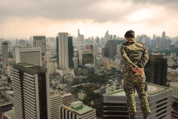 Back view. Soldier in camouflage uniforms, hands behind his backs on urban city background,democracy security concept.