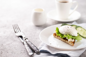 Breakfast with poached egg on toast and coffee