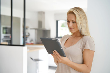 Middle-aged woman at home connected with digital tablet