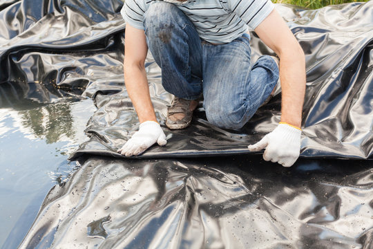 Close up view of worker in white gloves put a black vinyl sheet cover hole on the ground to be used as a pond for fish