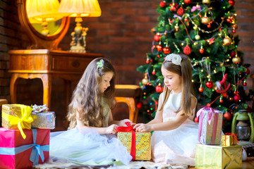 girls in beautiful dresses are sitting on the floor near the Christmas tree, open gifts