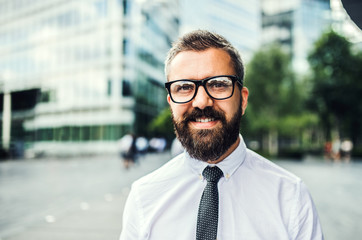 A close-up portrait of hipster businessman with glasses in the city.