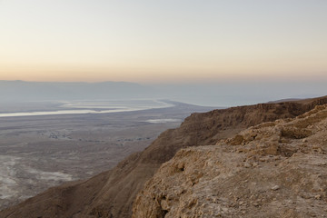 People at Masada fortress looking at the sunrise over the Dead Sea, Israel.