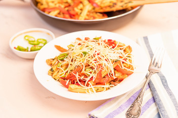 Italian food - Pasta with red pepper and parmesan on a white plate on a rustic light table