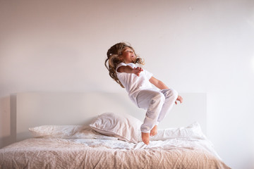 A little girl (kid) jumps on the bed of her parents. Concept: freedom, happiness, family