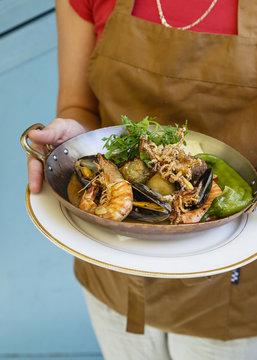 Waiter holding seafood at a restaurant, Jerusalem, Israel.