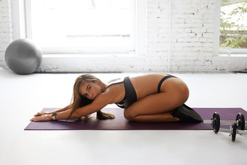 Side view of professional woman training on mat, stretching her body, doing flexibility exercises in sneakers and underwear, looking at camera. Slim flexible female in lingeries practicing yoga
