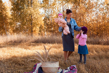 A young female mother in a jeans jacket and dress is holding her daughters and enjoying nature, posing and talking to them on the back of a background of autumn field landscape and yellow trees.