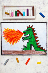 Colorful hand drawing: dragon spitting fire. Fire breathing dragon on paper.