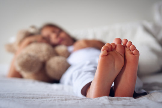 Close up of the feet of a young girl (kid) while she is sleeping on her bed with the teddy bear
