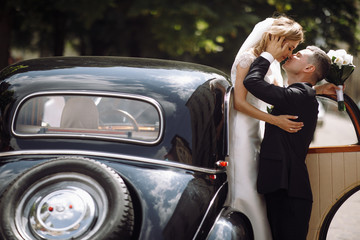 Groom holds bride in his arms hugging with her before a black retro car