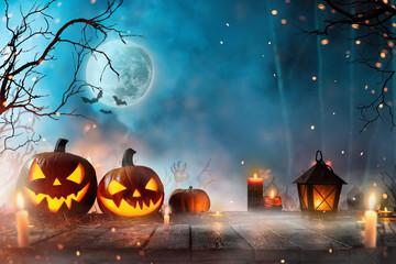 Halloween pumpkins on dark spooky forest.