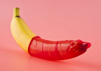 yellow banana with a red condom on a pink background