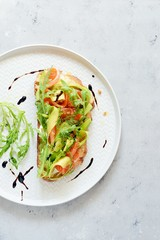 Brusctta with avocado, salmon, fresh leaves of arugula and balsamic. Breakfast with fresh organic greens, snacks, gravlax