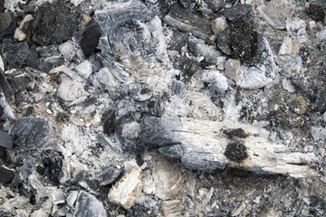 Burnt coals with grey ash after extinguished fire for barbeсue, natural background or texture