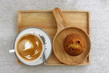 Above view of a blueberry muffin and a cup of coffee latte with heart designs in the froth all on a wooden board.