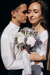 Groom holds bride tender kissing in the shadow