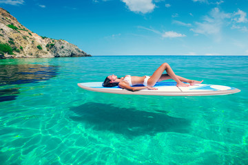 Poster Ontspanning Young beautiful woman relaxing in the sea on a SUP board. The girl sunbathes on the beach of the island on vacation.