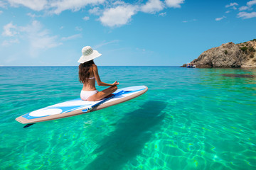 A beautiful young woman relaxes on a SUP board in the sea near the island. Standup paddleboarding on Hawaii.