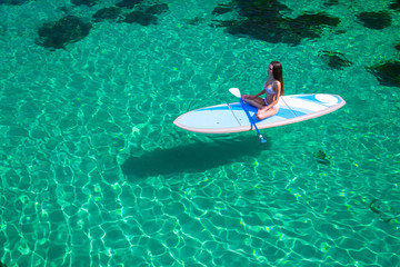 Young beautiful woman in a bikini on a SUP board in the sea.Young attractive woman meditating on the sup board in the sea. Girl in meditative pose on water.