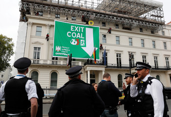 Police officers stand by as Greenpeace activists abseil down the facade of Germany's embassy, unfurling a banner against coal, in London