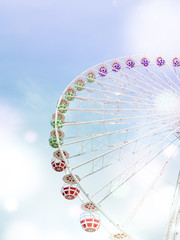 ferris wheel on the background of blue sky with colorful circles