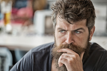 Man brutal bearded hipster thoughtful face defocused background. Macho with beard and mustache look confident brutal. Beard represent masculinity. Think and realize. Beard masculinity attribute