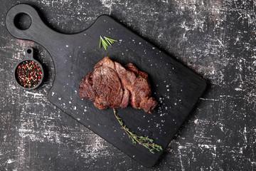 стейк из говядины с тимьяном и розмарином на сервировочной доске