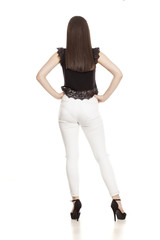 back view od young woman in white jeans and high heels on white background