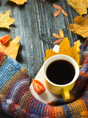 Autumn comfort. Mug of hot coffee with a colorful scarf with colorful autumn leaves on wooden background copy space