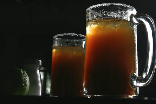 Two michelada jars which are a Mexican beverage made with beer, lime juice, and assorted willows, spices, and peppers. It is served in a chilled, salt-rimmed glass.